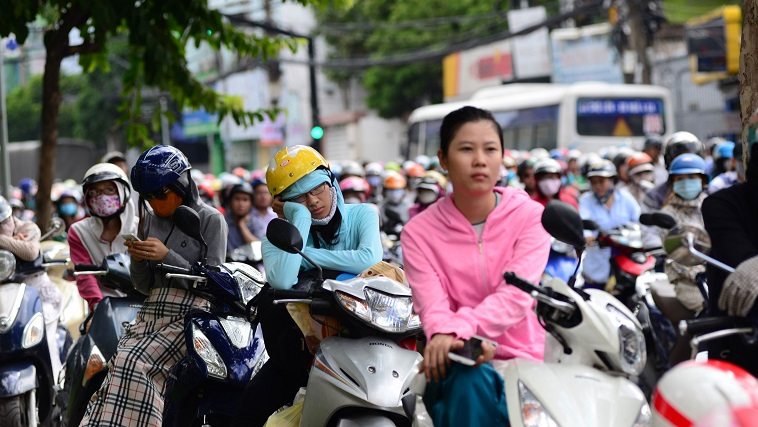 People park their motorcycles along the road, waiting for the traffic jam to dissipate.