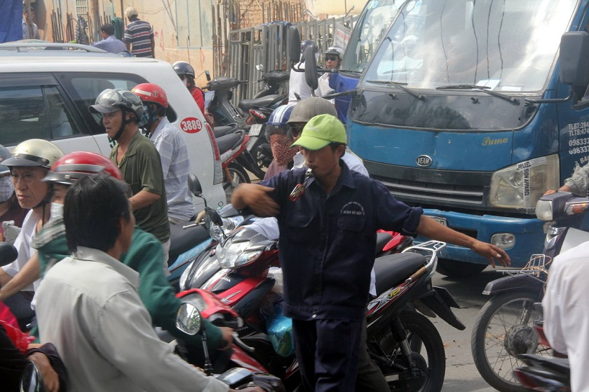 A garbage collector attempts to control the flow of traffic, preventing people from traveling on the wrong lanes.