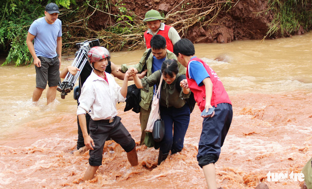 Reporters and members of the Red Cross in Lai Chau cross a stream to help locals in Noong Heo Commune.