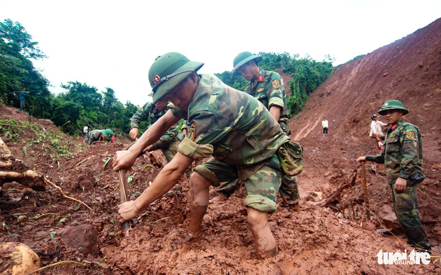 Soldiers from Regiment 880 dig under layers of mud to look for missing victims.