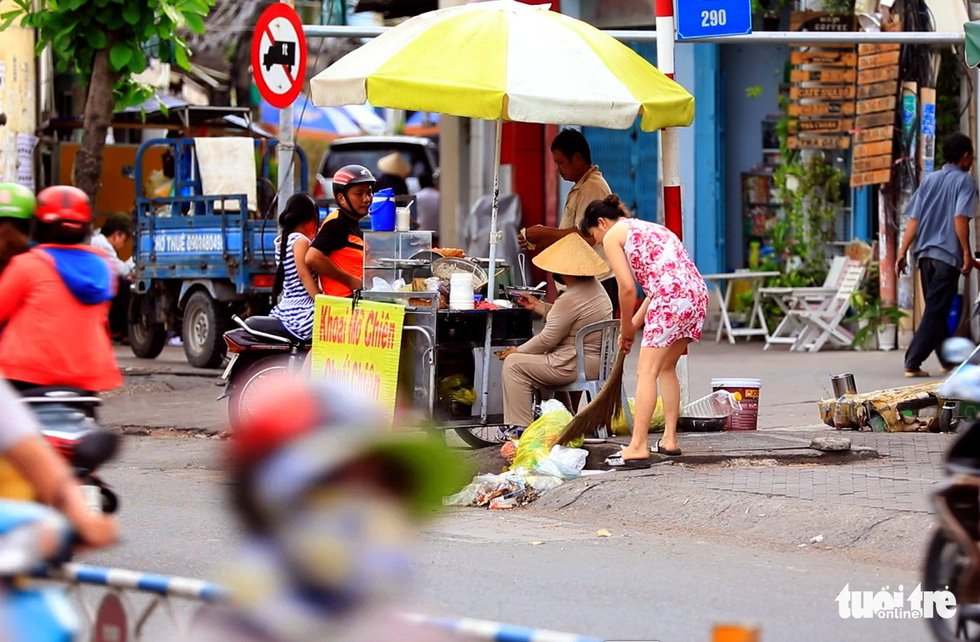 A woman sweeps rubbish in front of her house before piling it up at a nearby sewer entrance on Duong Ba Trac Street in District 8, Ho Chi Minh City. Photo: Tuoi Tre