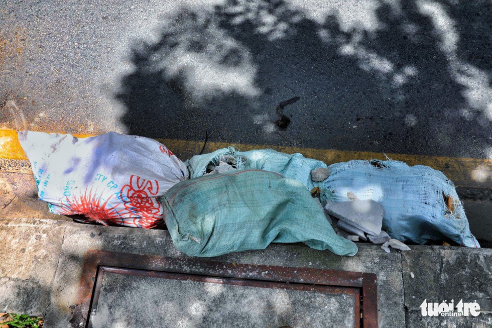 Garbage, along with a broom, is dumped at a sewer on Trinh Hoai Duc Street in Binh Thanh.