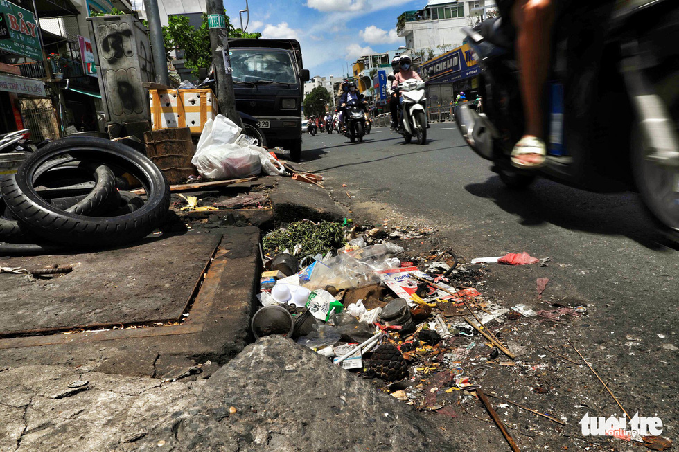All types of trash block the entrance of a drain on Ly Thai To Street in District 3.