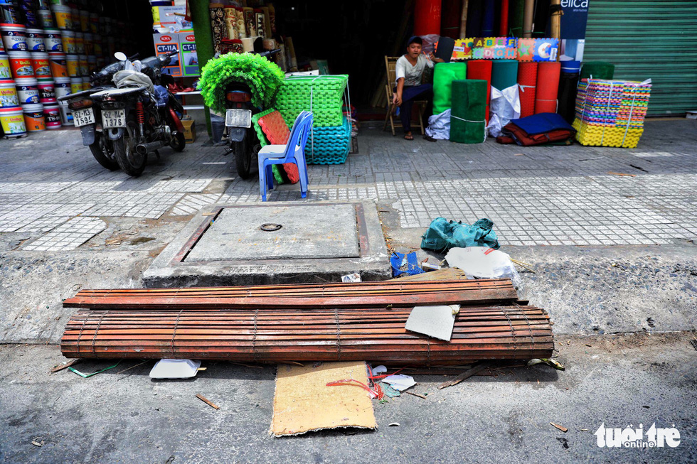 A used bamboo mattress blocks the entire entrance of a sewer.