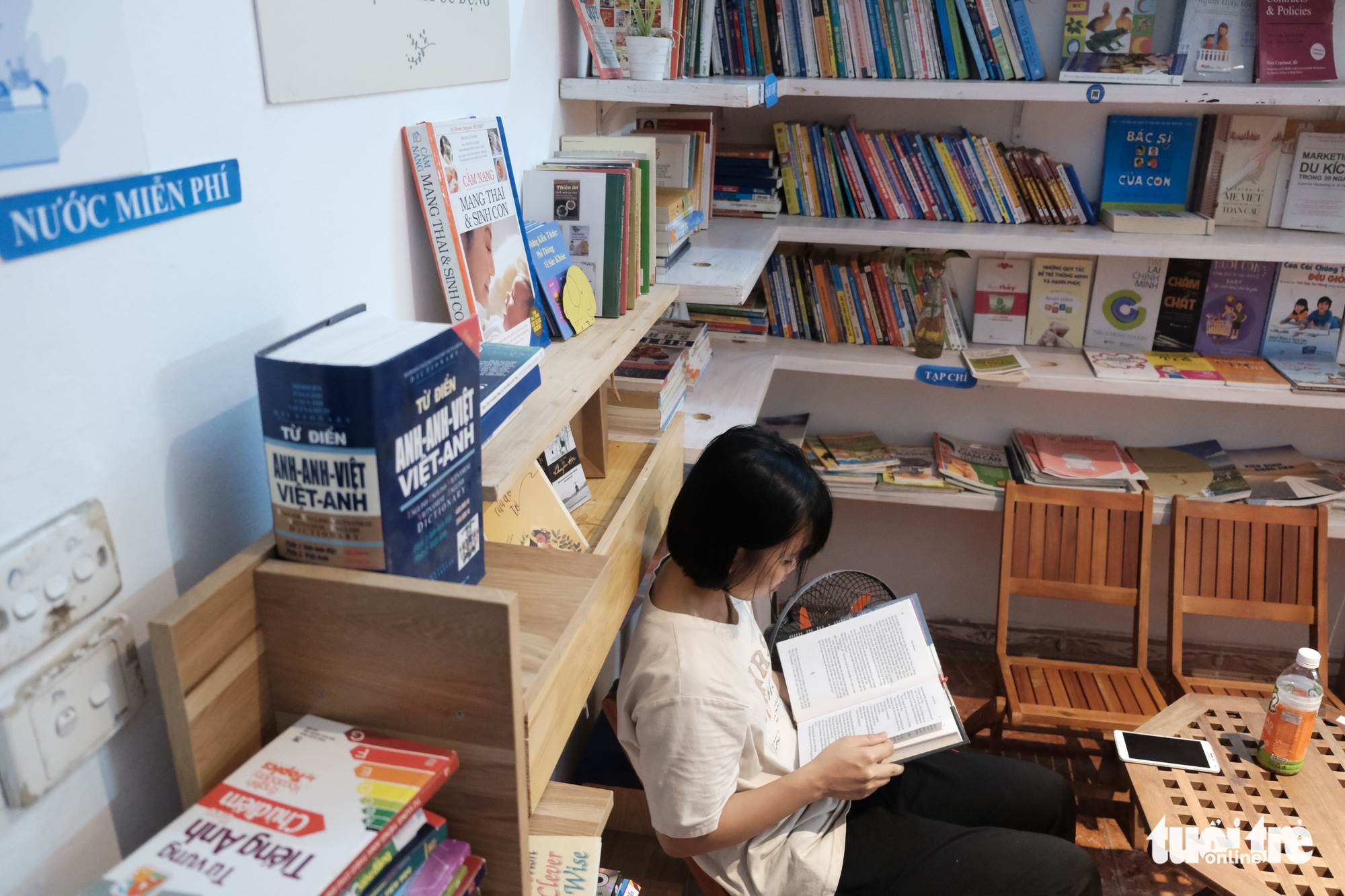 A girl reads a book at the 'free aid combo' store at No. 66 Chua Lang Street, Dong Da District, Hanoi, Vietnam. Photo: Song La / Tuoi Tre
