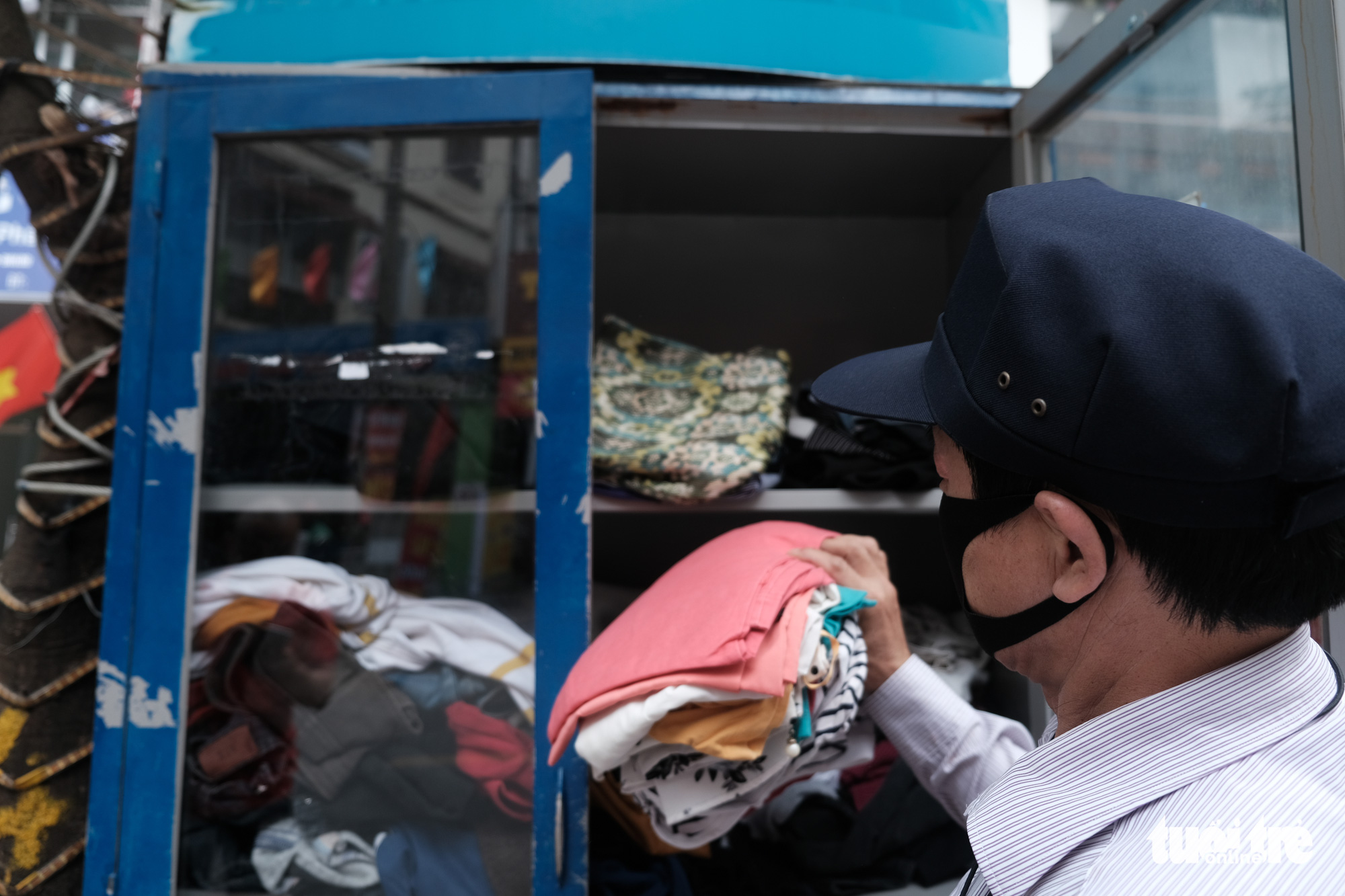 Tran Xuan Trieu, the security guard at a charitable store in Hanoi, Vietnam, checks on the store's free clothes cabinet. Photo: Song La / Tuoi Tre