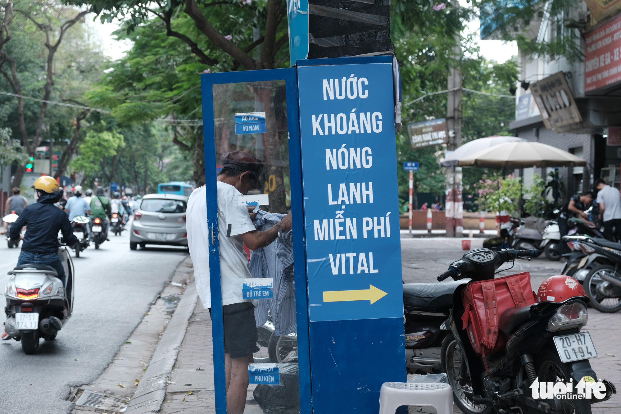 A man picks clothes from a free clothes cabinet outside a store in Hanoi, Vietnam. Photo: Song La / Tuoi Tre