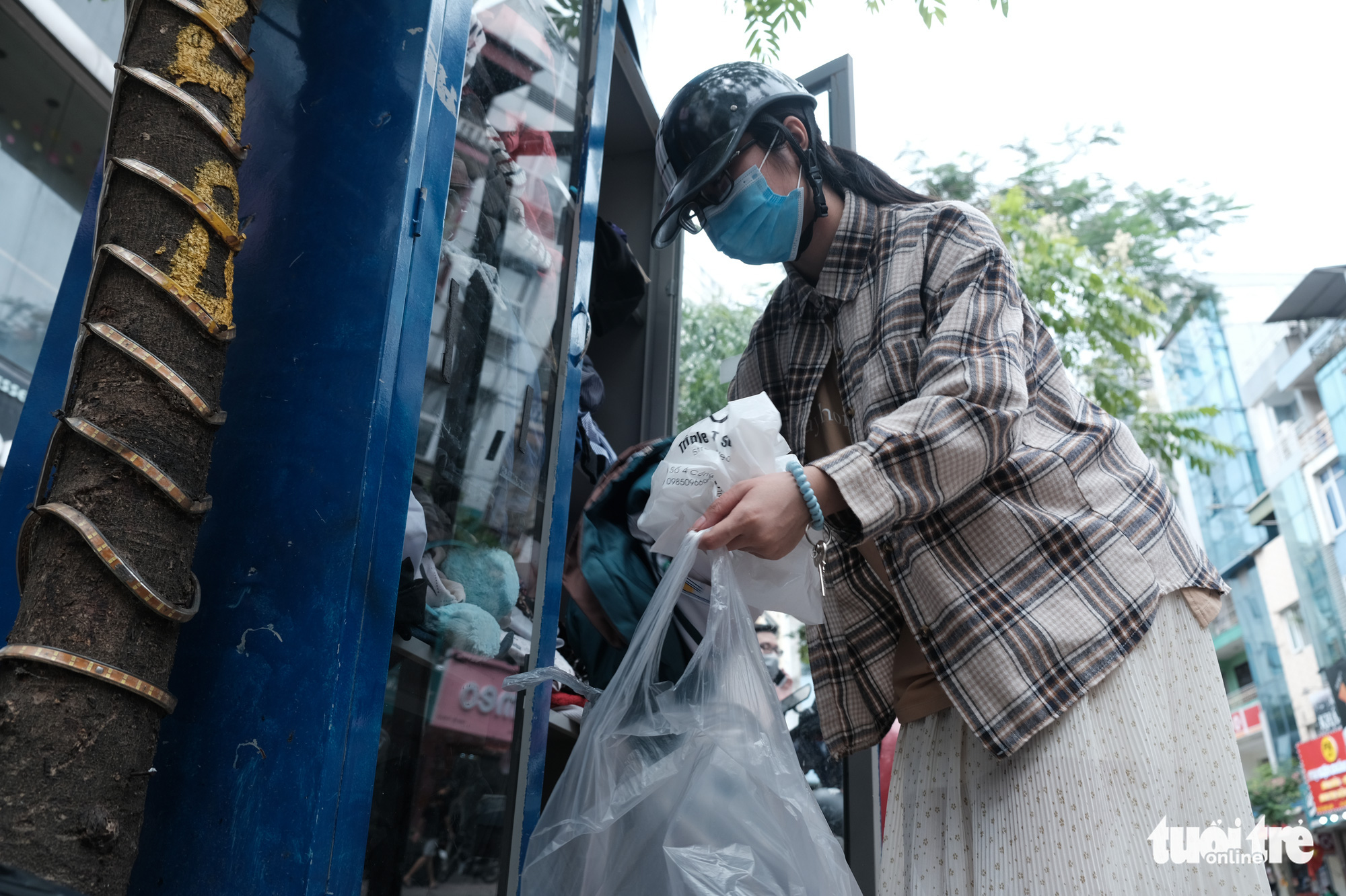 Donor Nguyen Thu Huyen donates her clothes to a free clothes cabinet outside a store in Hanoi, Vietnam. Photo: Song La / Tuoi Tre