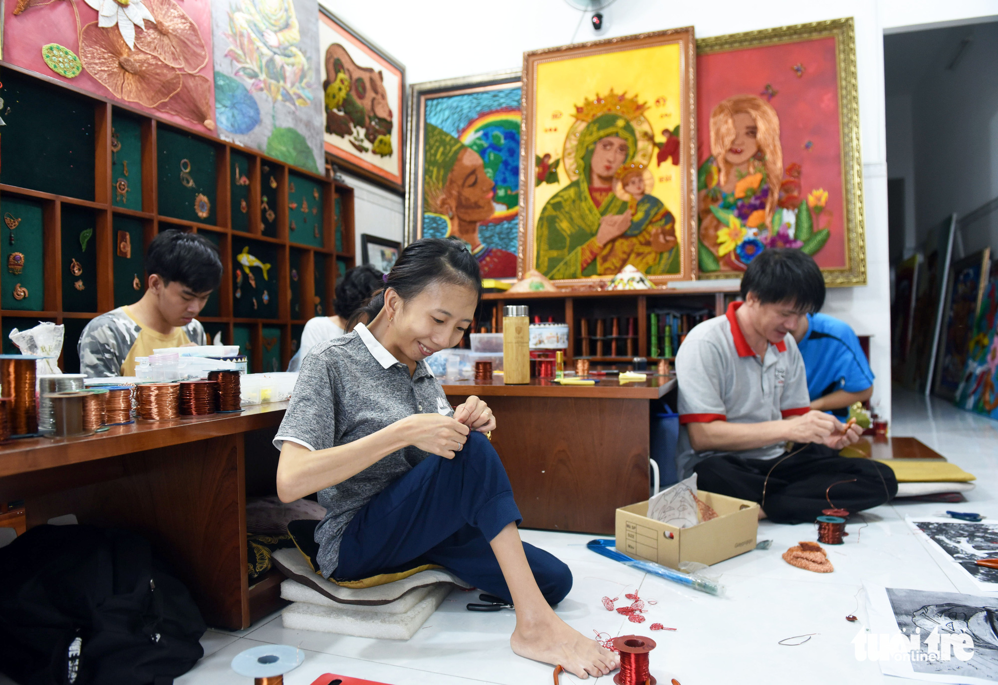 Duong Thi My Huyen (left) from Quang Ngai Province, a disabled artist with muscular atrophy, works on a piece at Nguyen Thi Nhat Phuong's copper wire art class in Ho Chi Minh City, Vietnam. Photo: Duyen Phan / Tuoi Tre