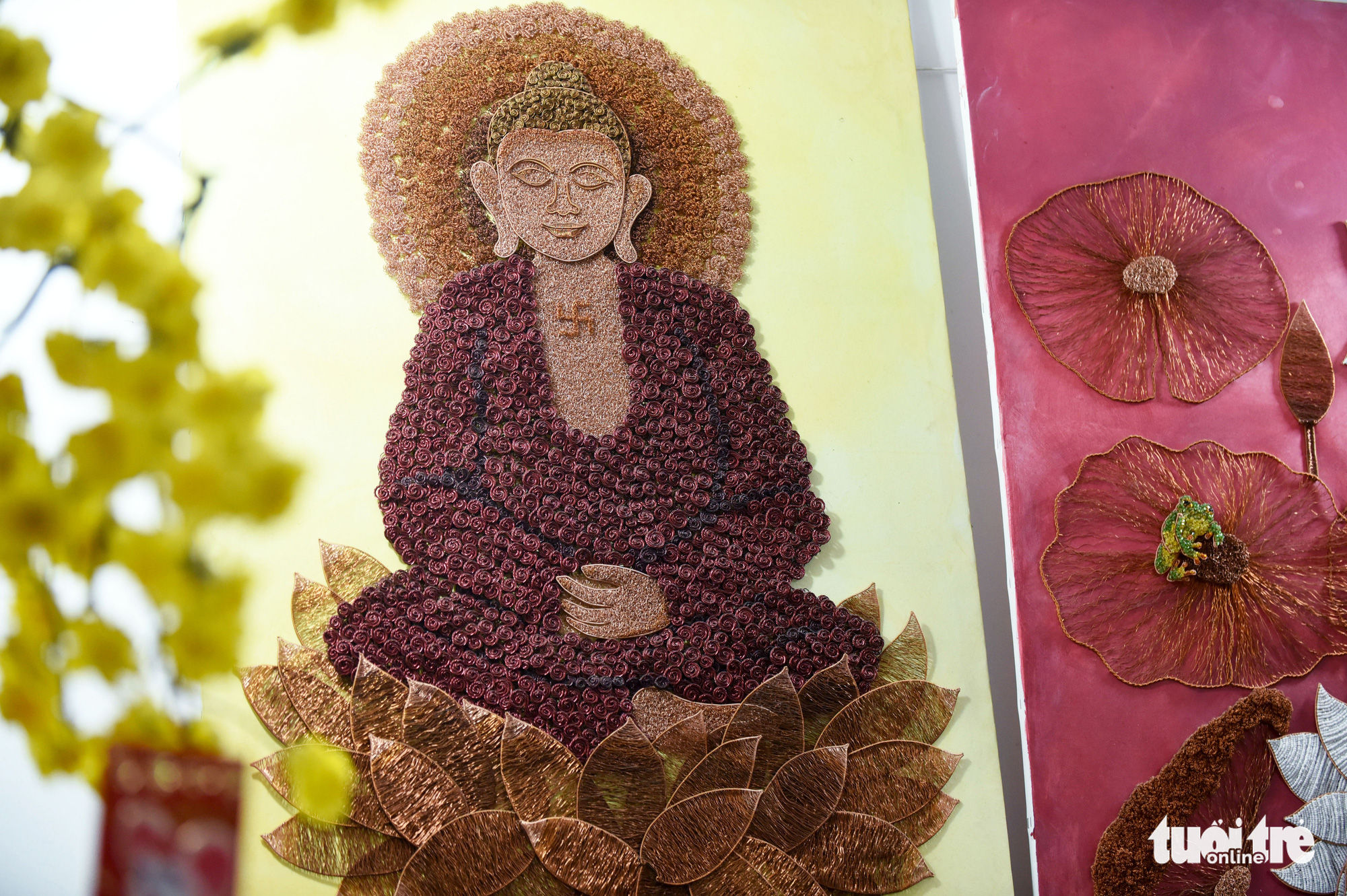 A caricature of Buddha sitting on a lotus flower is depicted in this copper wire art piece. Photo: Duyen Phan / Tuoi Tre