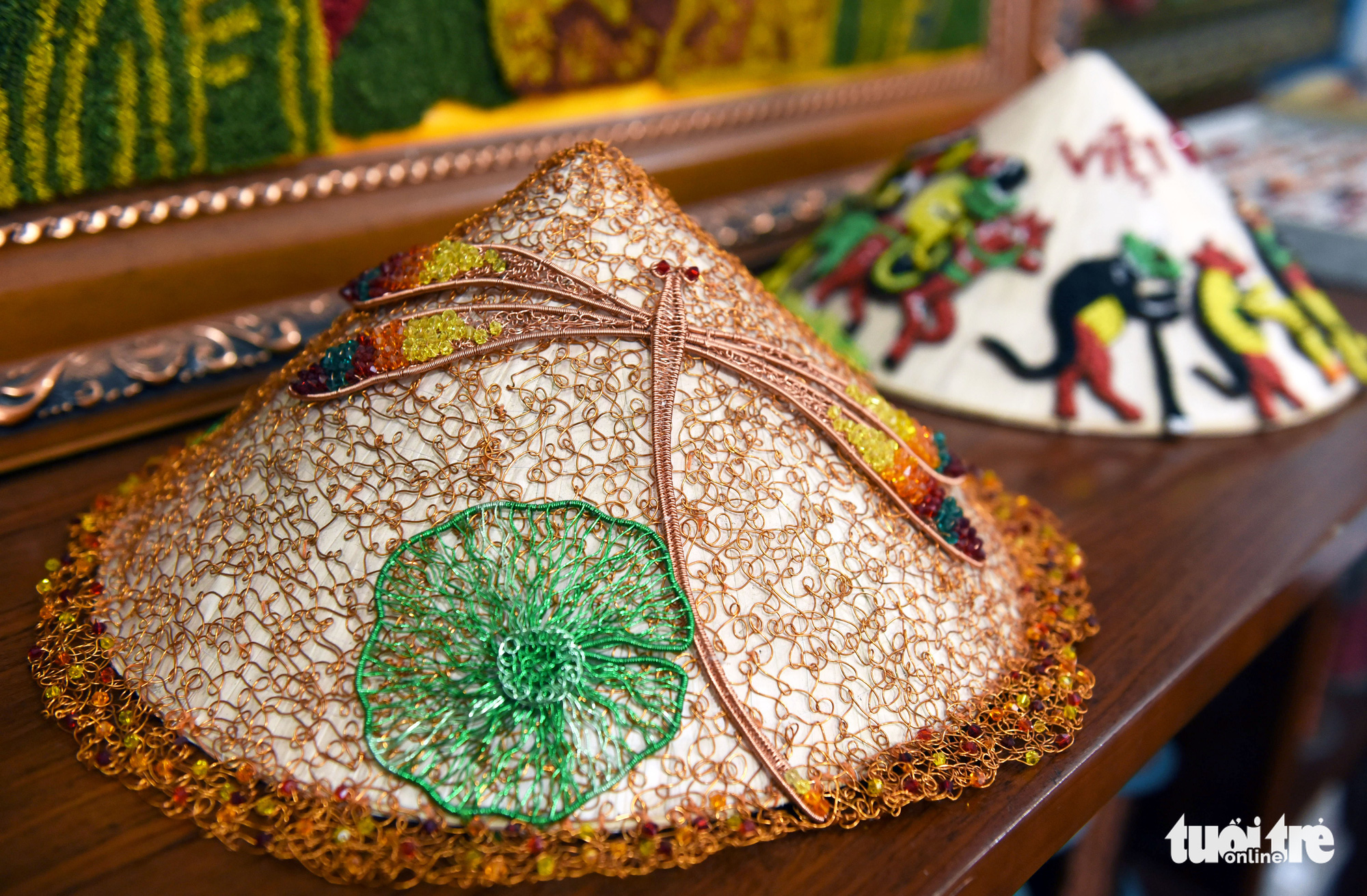 A copper wire lotus leaf and dragonfly decorate a traditional Vietnamese 'non la' conical hat at an art class in Ho Chi Minh City, Vietnam. Photo: Duyen Phan / Tuoi Tre