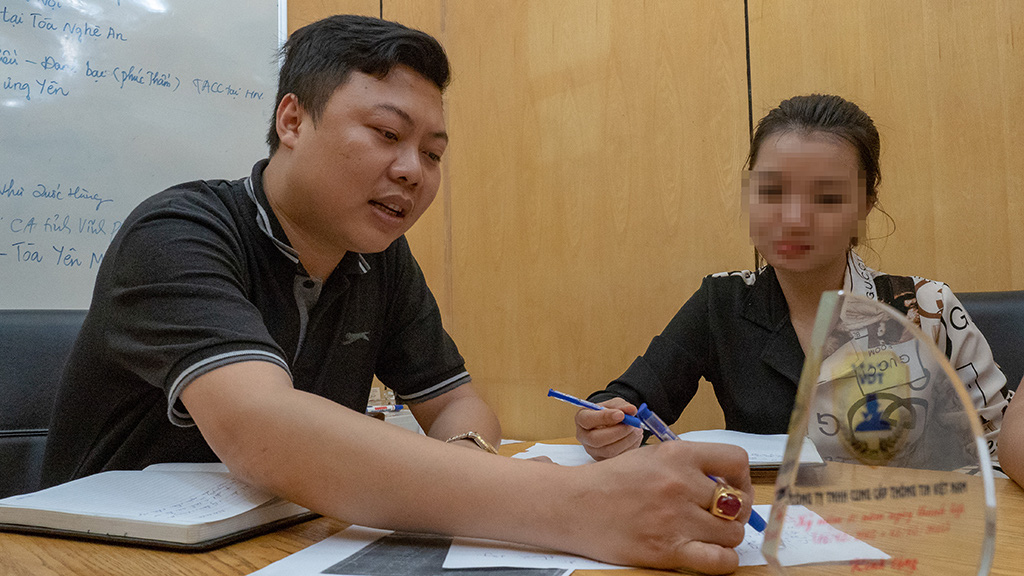 Ngoc Anh (left) discusses how to approach a target with a fellow detective. Photo: Vu Tuan / Tuoi Tre
