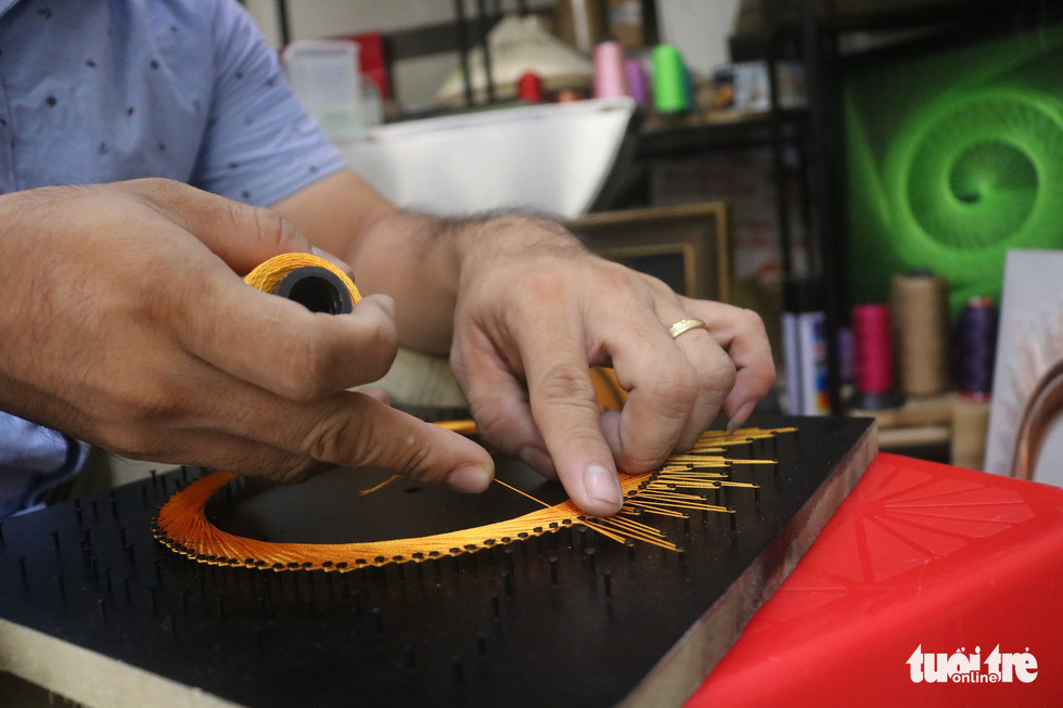 Phan Ba Thanh makes a string art. Photo: Thu Hien / Tuoi Tre