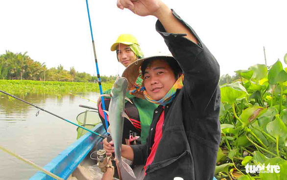Vo Hien Luong (black shirt), from Long My District in Hau Giang Province, located in Vietnam's Mekong Delta, is thrilled with his catch. Photo: Chi Cong/ Tuoi Tre
