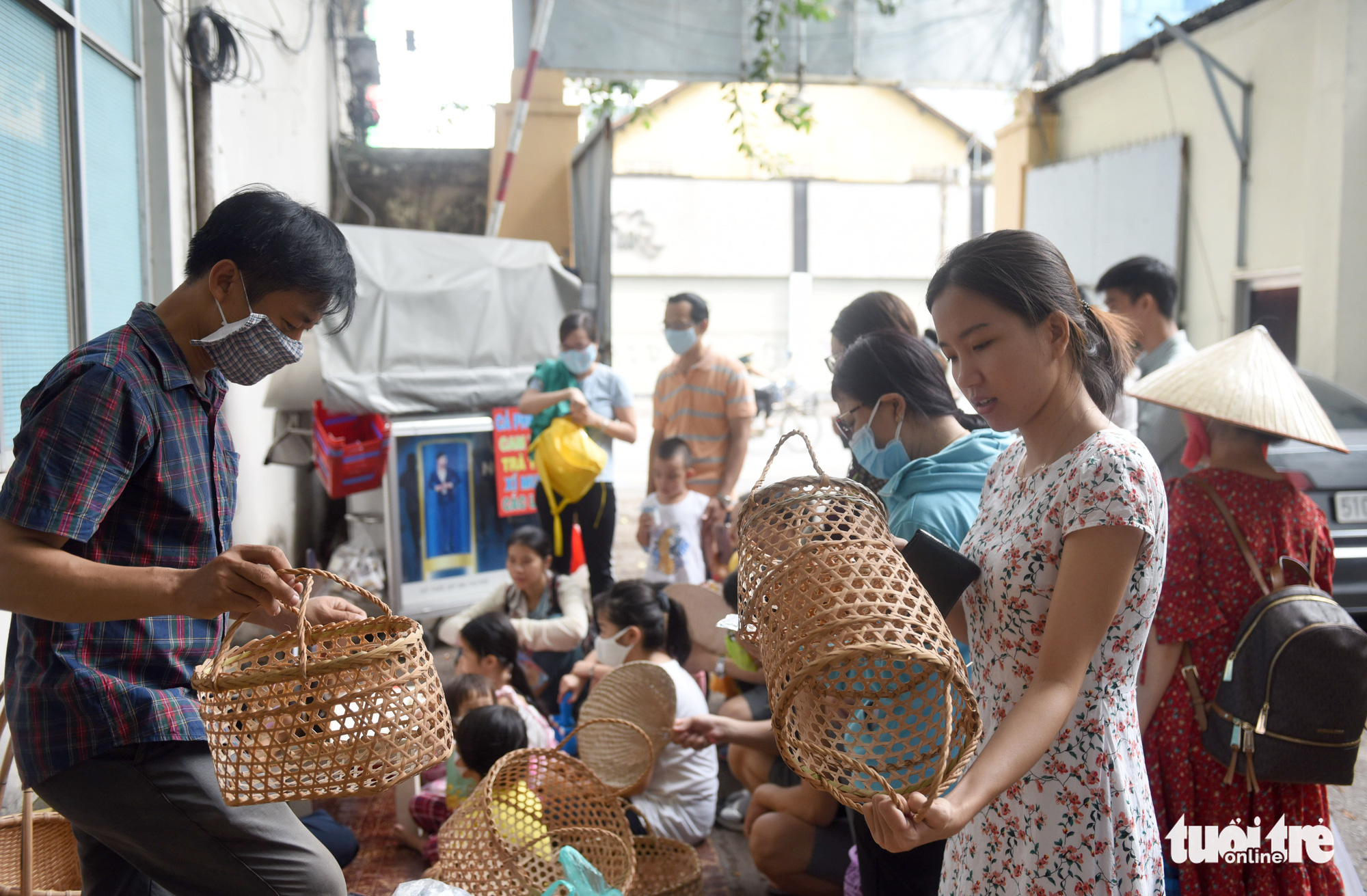 Nguyen Anh Thu (right) selects handmade baskets at a 'countryside market' at No. 7 Nguyen Thi Minh Khai Street, District 1, Ho Chi Minh City, Vietnam, May 24, 2020. Photo: Duyen Phan / Tuoi Tre