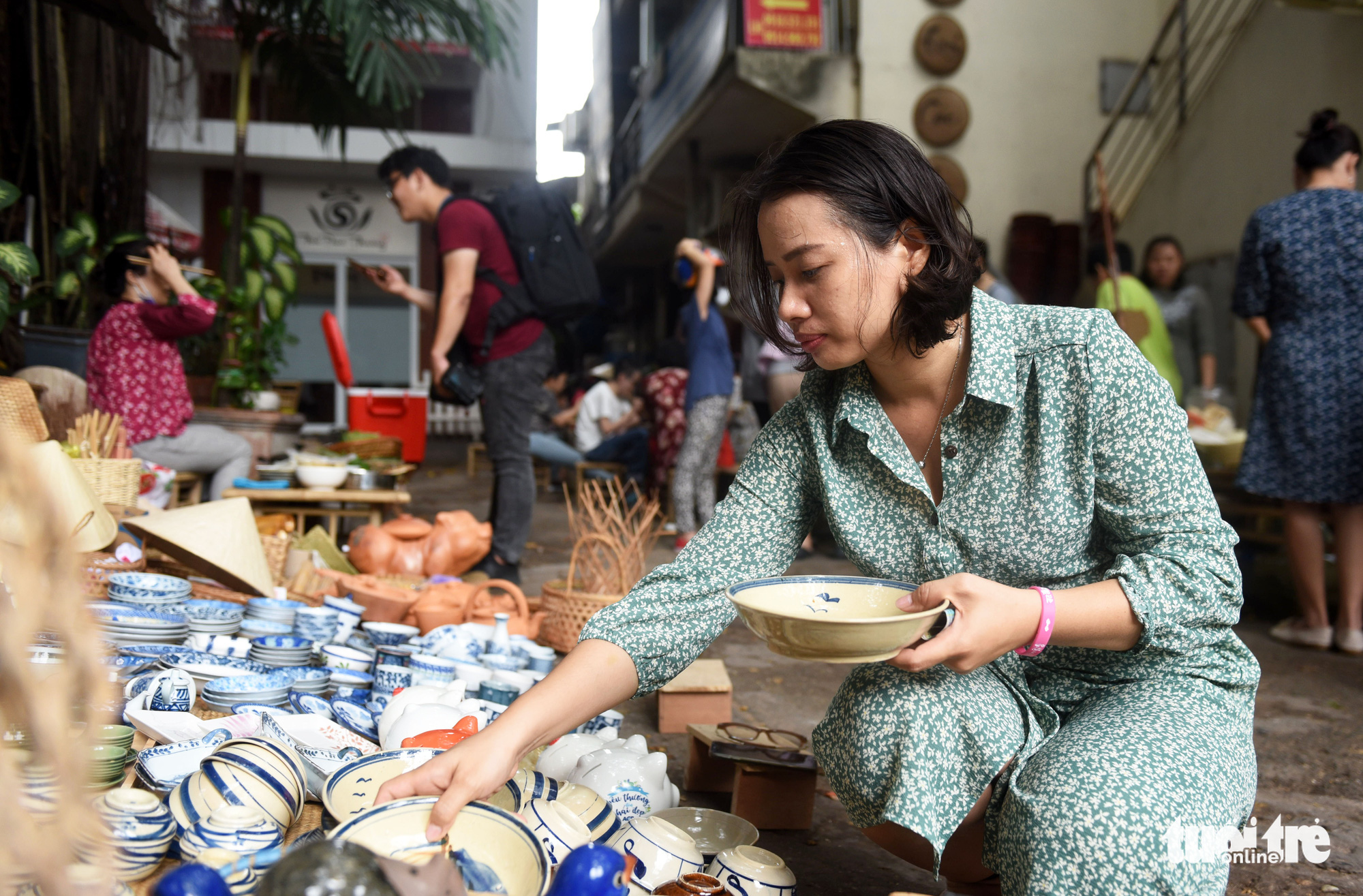 Truong Thi Ngoc Nhung selects pottery dinnerware at a 'countryside market' at No. 7 Nguyen Thi Minh Khai Street, District 1, Ho Chi Minh City, Vietnam, May 24, 2020. Photo: Duyen Phan / Tuoi Tre