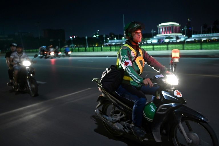 Pham Quoc Viet, who works for ride-hailing firm Grab by day but turns an unofficial emergency responder at night, patrols a street in Hanoi on his motorbike. Photo: AFP