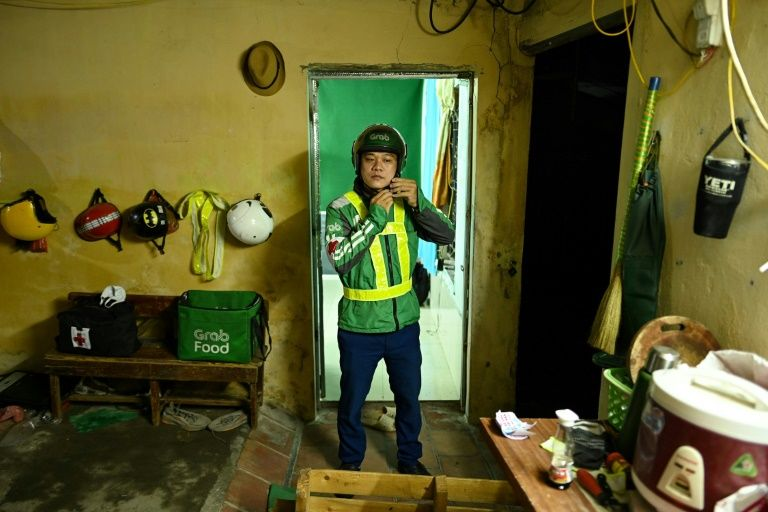 Pham Quoc Viet, who works for ride-hailing firm Grab by day, is pictured before he leaves his house to work as an unofficial emergency responder at night. Photo: AFP