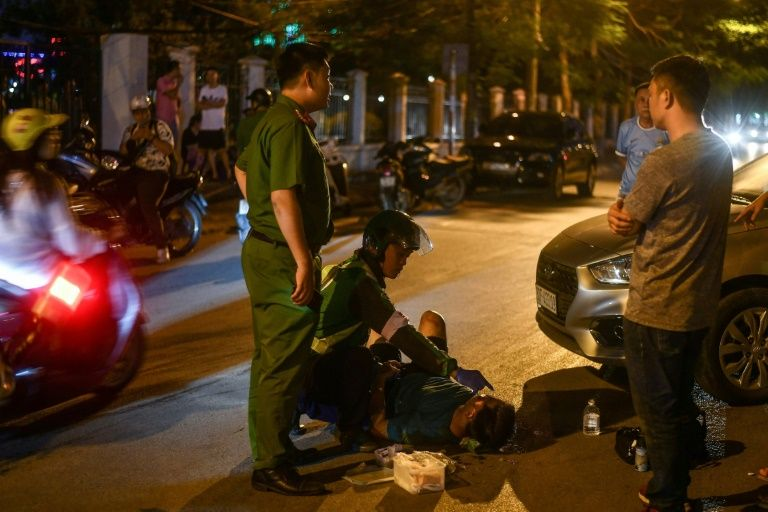 An unofficial emergency responder and a police officer are seen at the scene of a traffic accident in Hanoi. Photo: AFP