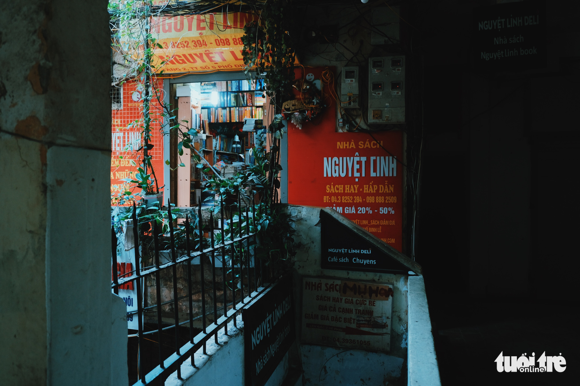 Stairs lead to the first floor of an old apartment building at No. 5 Dinh Le Street, Hanoi, Vietnam with posters advertising the bookstores' promotions. Photo: Song La / Tuoi Tre
