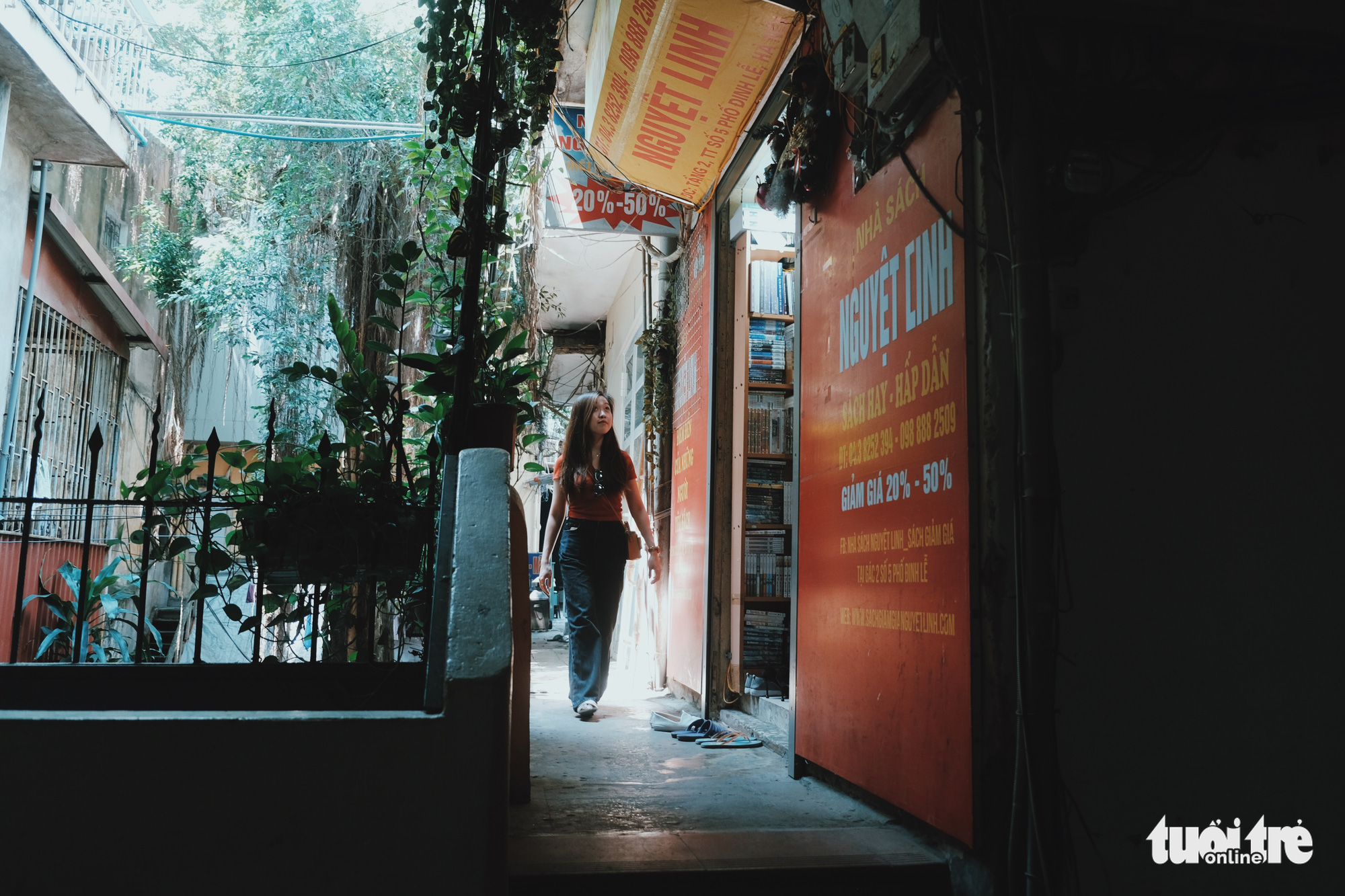 A girl walks past the Nguyet Linh bookstore located on the first floor of an old apartment building at No. 5 Dinh Le Street, Hanoi, Vietnam. Photo: Song La / Tuoi Tre