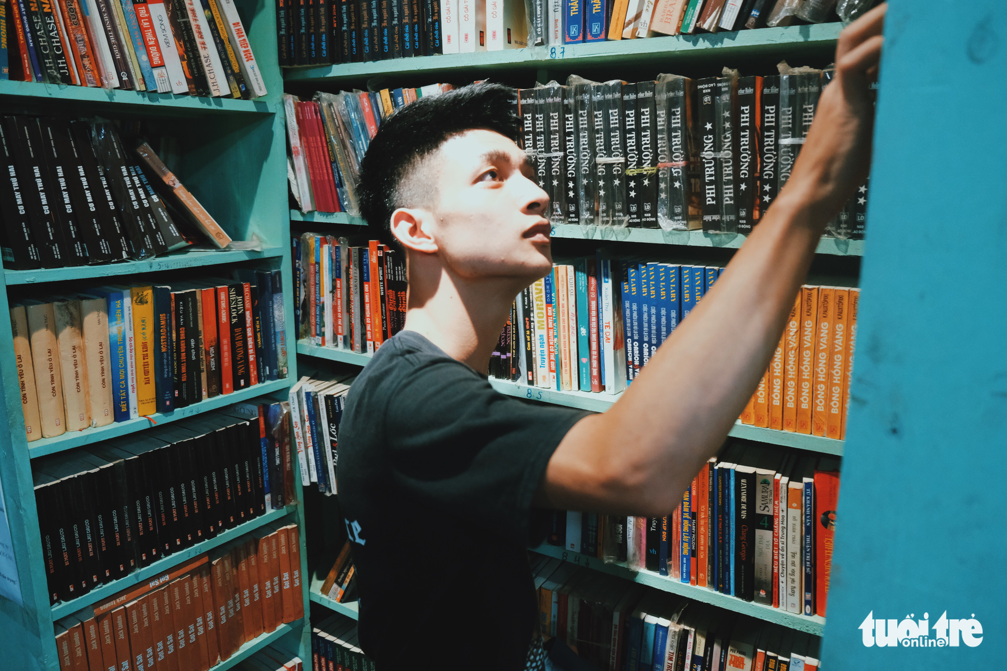 Duc Anh, who comes to a bookstore at No. 5 Dinh Le Street, Hanoi, Vietnam for the first time with his girlfriend, looks at books on a bookshelf. Photo: Song La / Tuoi Tre