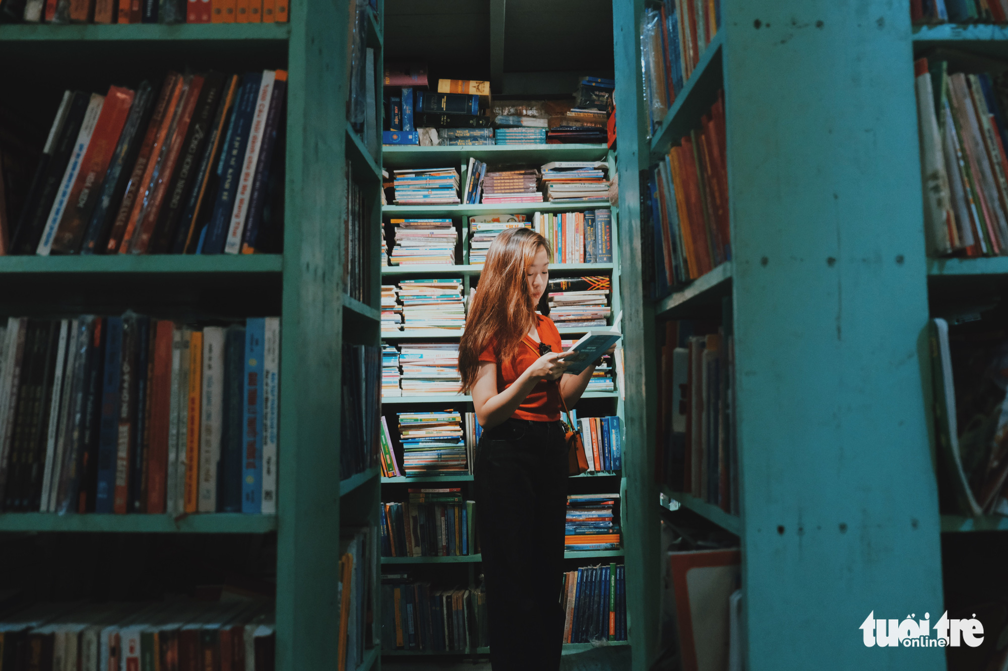 A girl reads a book at a bookstore at No. 5 Dinh Le Street, Hanoi, Vietnam. Photo: Song La / Tuoi Tre