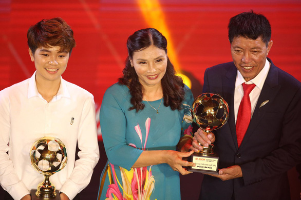 Doan Van Hau's father (right) receives the the best young male player prize on behalf of his son and Nguyen Thi Tuyet Ngan (left) receives the the best young female player prize at the 2019 Vietnam Golden Ball awards ceremony in Ho Chi Minh City, May 26, 2020. Photo: N.K. / Tuoi Tre