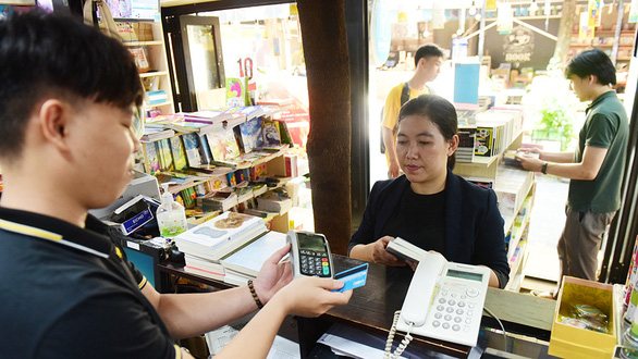 A woman makes a cashless payment at a bookstore on Nguyen Van Binh Street in District 1, Ho Chi Minh City, Vietnam, May 26, 2020. Photo: Quang Dinh / Tuoi Tre