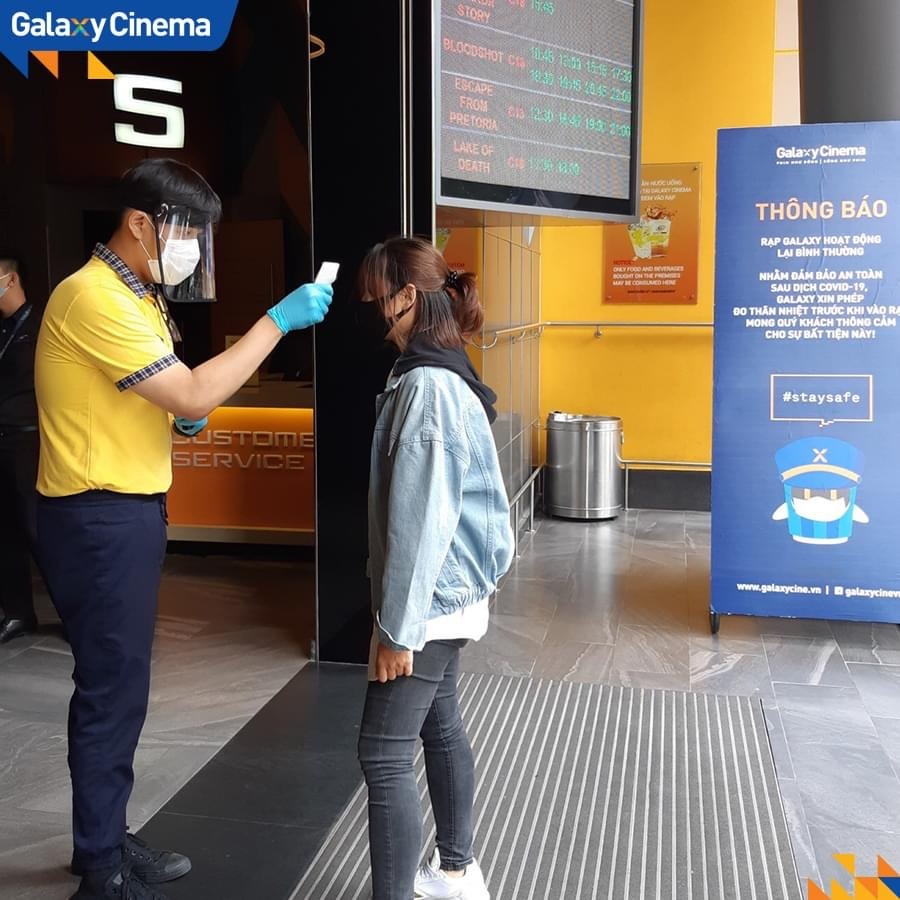 <em>An attendant checks the body temperature of a movie-goer at a Galaxy Cinema theater in Ho Chi Minh City, Vietnam in this photo posted to the cinema chain's verified Facebook page.</em>