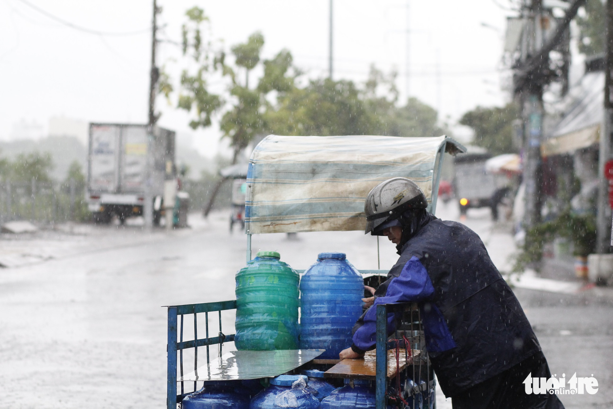 A man delivers water bottles under the rain in District 7, Ho Chi Minh City, May 30, 2020. Photo: Chau Tuan / Tuoi Tre