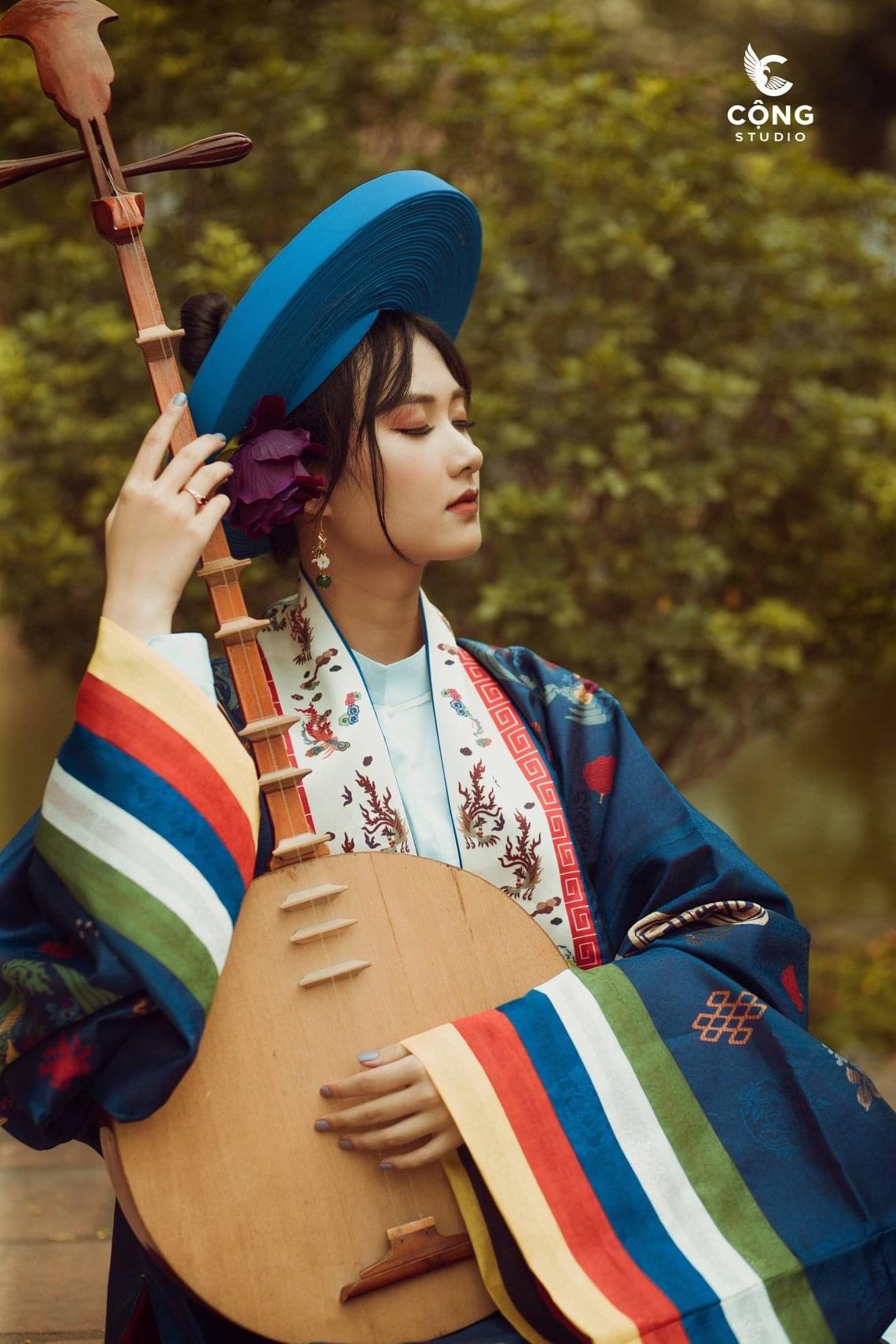 A female student wears a 'nhật bình' dress and holds a 'đàn kìm,' a traditional Vietnamese double-stringed lute, in this supplied yearbook photo.
