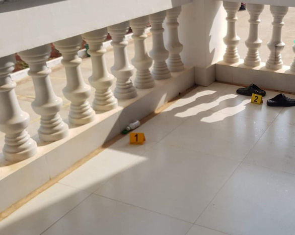 A can suspected of containing a pesticide (1) and a pair of sandals (2) are left on the second floor of a courthouse in Binh Phuoc Province, Vietnam, where Luong Huu Phuoc jumped to his death on May 29, 2020. Photo: T.D. / Tuoi Tre