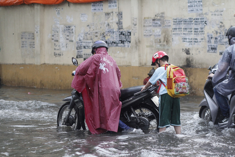 A man walks his broken-down motorbike on a flooded street after a heavy rain in Ho Chi Minh City, June 3, 2020. Photo: Chau Tuan / Tuoi Tre