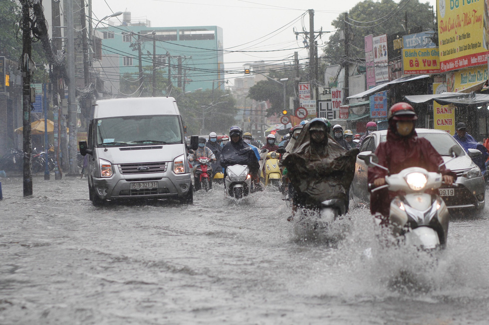 Vehicles travel on a flooded street after a heavy rain in Ho Chi Minh City, June 3, 2020. Photo: Chau Tuan / Tuoi Tre