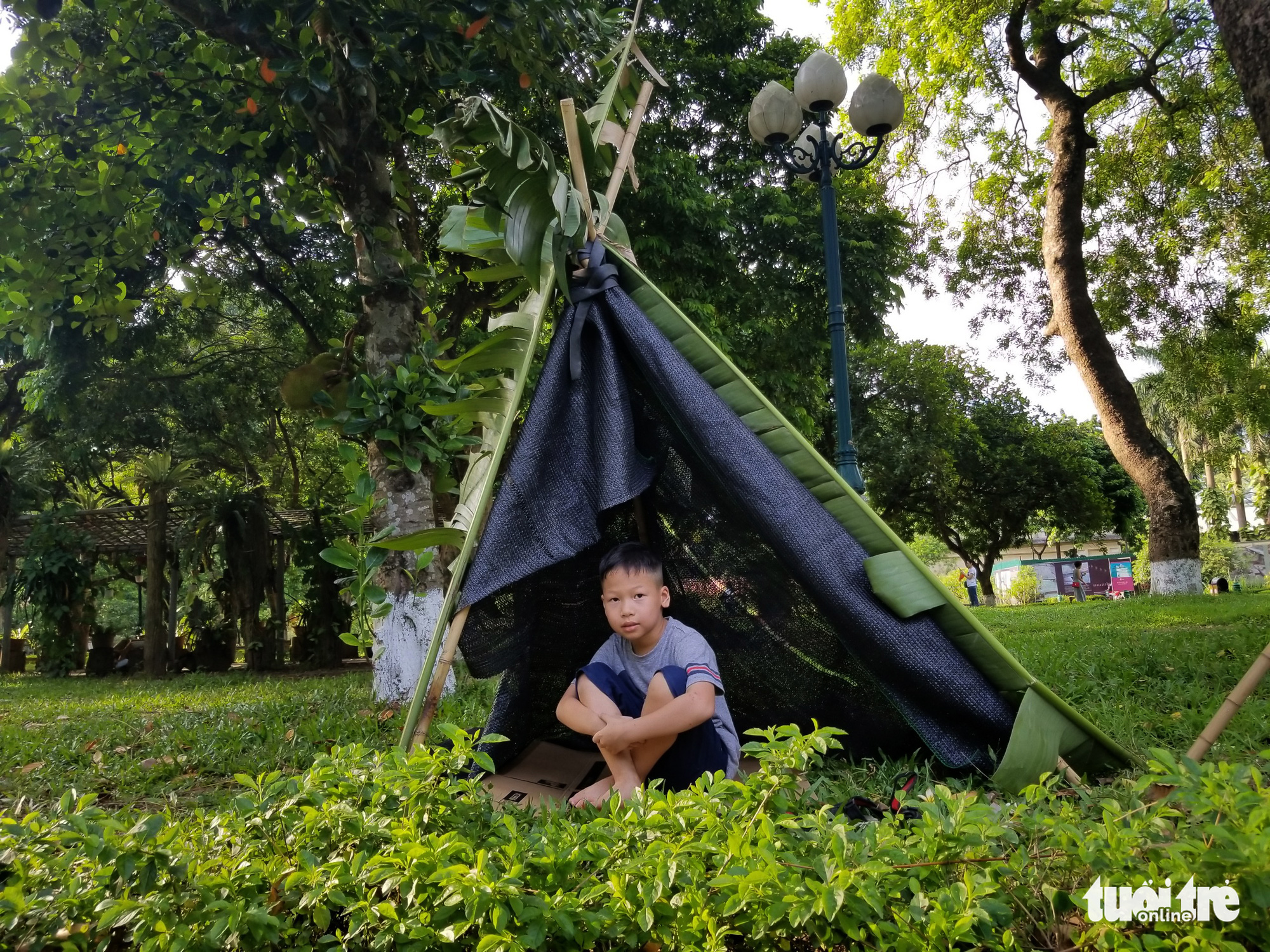 A boy sits in a tent made from banana leaves at the 'Kingdom of Recycled Materials' event in Hanoi, Vietnam, May 31, 2020. Photo: Ha Thanh / Tuoi Tre