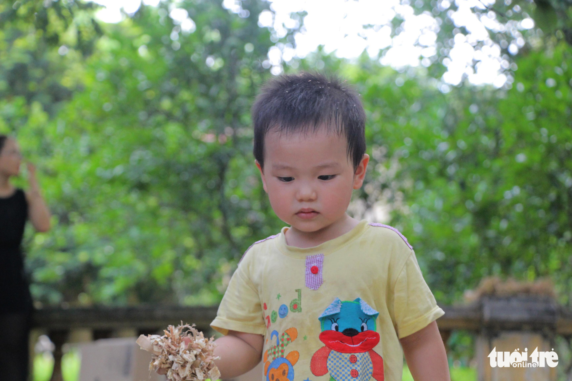 Moc, a two-year-old boy, holds sawdust in his hand at the 'Kingdom of Recycled Materials' event in Hanoi, Vietnam, May 31, 2020. Photo: Ha Thanh / Tuoi Tre