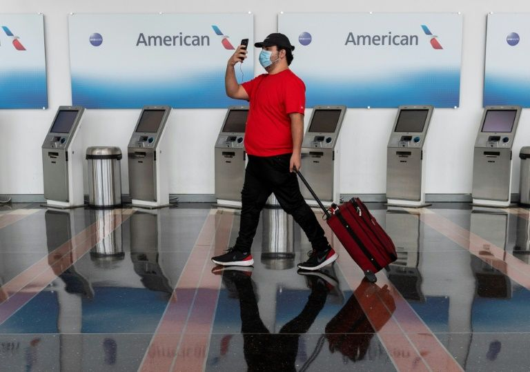 A passenger walks past American Airlines check-in terminals at Ronald Reagan National Airport in Washington, Arlington, Virginia in this photo taken on May 12, 2020. Photo: AFP
