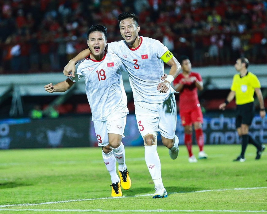 Attacking midfielder Nguyen Quang Hai (left) and defender Que Ngoc Hai react after the latter scores the second goal for Vietnam at a World Cup qualifier against hosts Indonesia in Bali, October 15, 2019. Photo: Vietnam News Agency