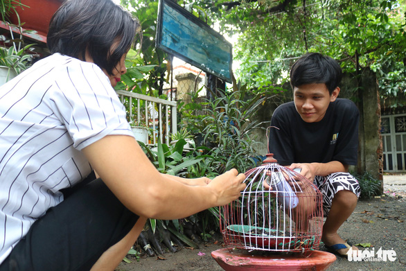 Tuan Khanh, Thuy's 15-year-old son, helps his mother transform a broken bird cage into a new ornament for their garden in Thu Duc District, Ho Chi Minh City, Vietnam. Photo: Ngoc Phuong / Tuoi Tre