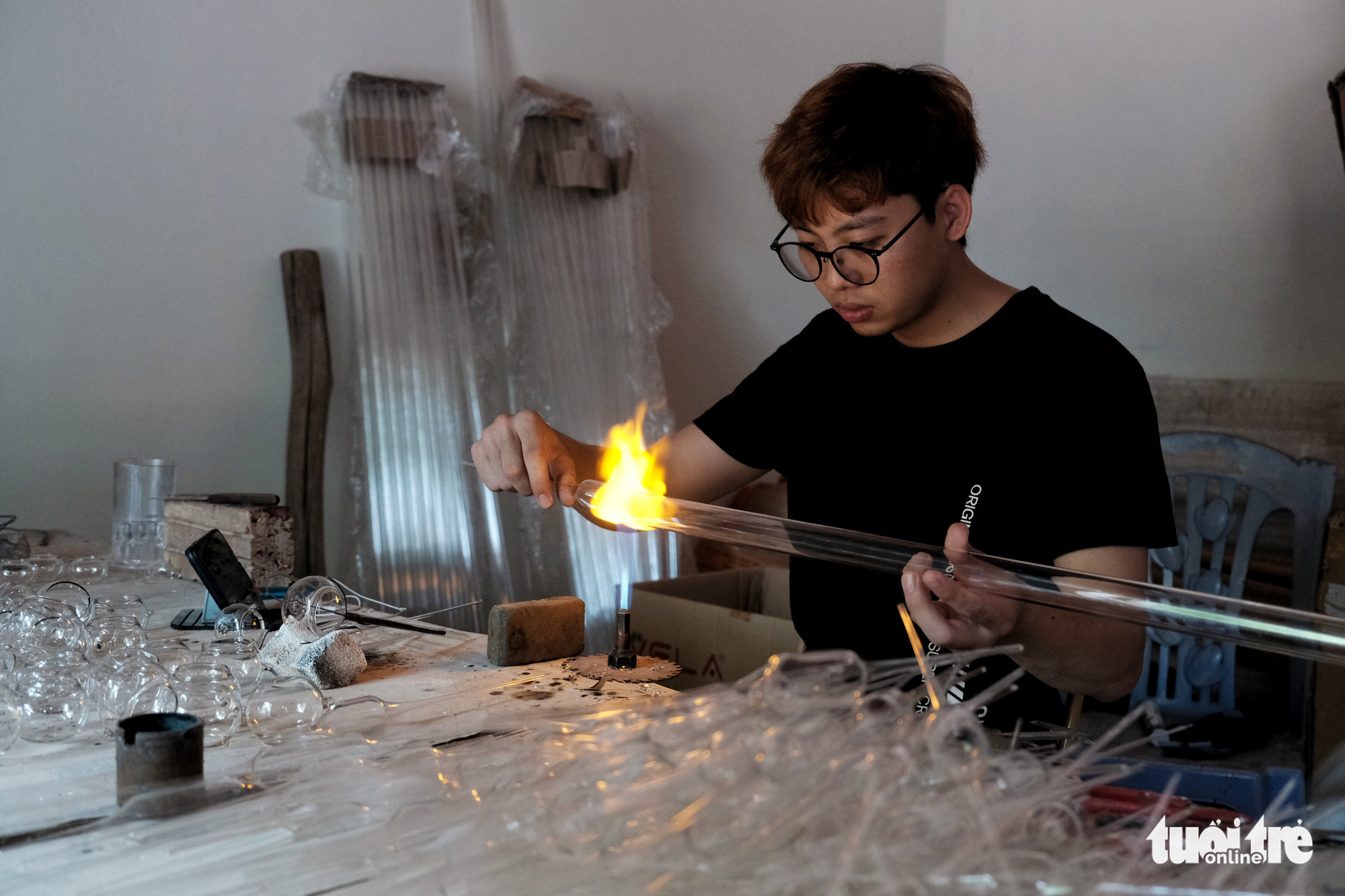 Making products out of glass requires many stages, including one which involves heating a glass tube to create shorter pieces. Photo: Mai Thuong / Tuoi Tre