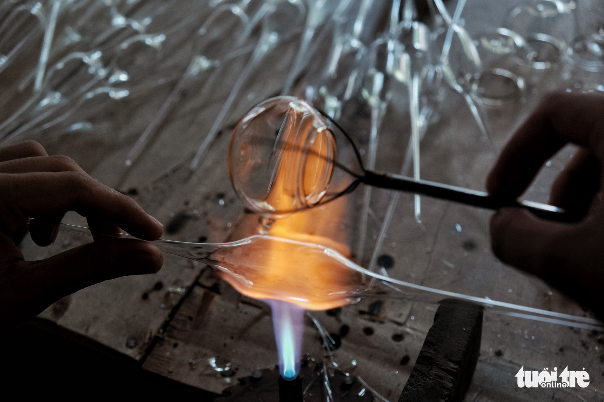 A skillful glass blower needs to know the 'ripeness' of glass. As glass is initially exposed to fire, it will appear blue in color before turning white. At that time, a slight blow is enough to mold the blob of molten glass into products of their desired shape, according to the professional glassmith Le Xuan Tien. Photo: Mai Thuong / Tuoi Tre