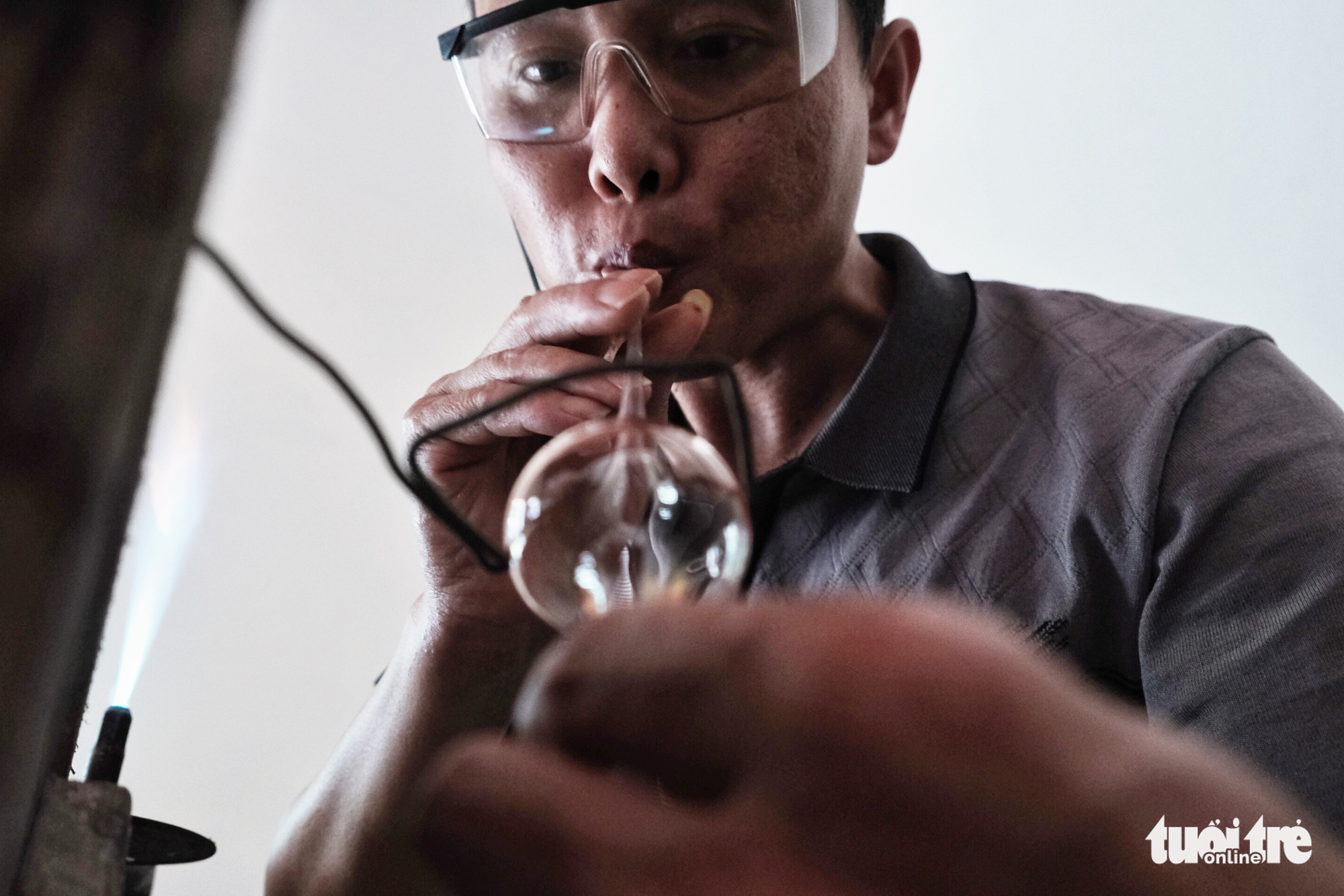 Molten glass is blown into a fixed mold so that a certain type of products will be in the same size. Photo: Mai Thuong / Tuoi Tre