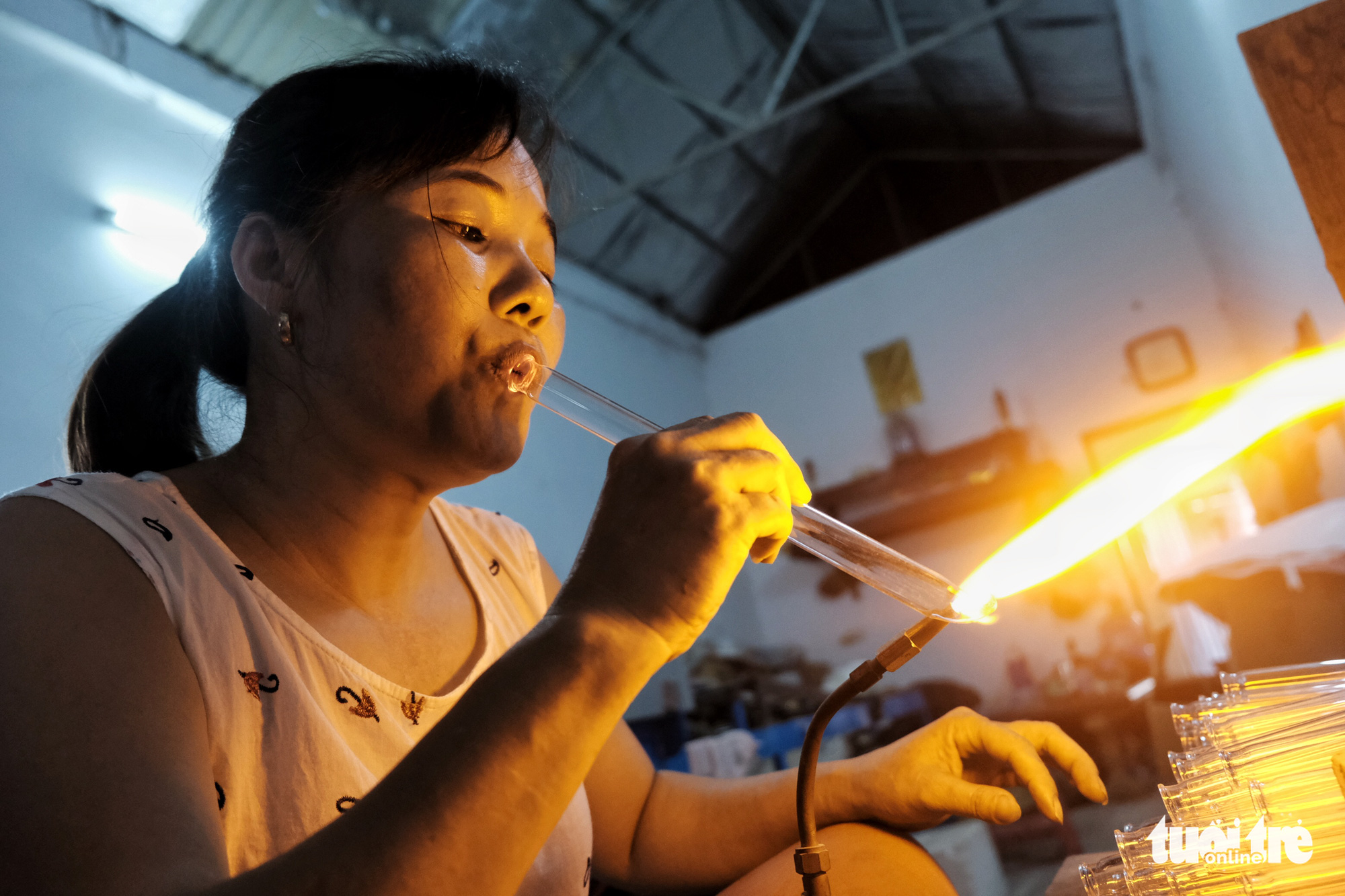 The family of Ta Thi Nga is among several households that still maintain the traditional glassblowing career at Hoang Xa Village, Thong Nhat Commune, Thuong Tin District on the outskirts of Hanoi, Vietnam. Her family produces test tubes, common pieces of laboratory glassware. Photo: Mai Thuong / Tuoi Tre
