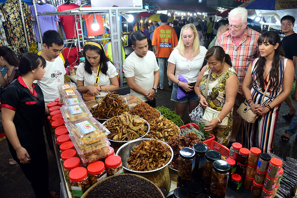 Foreign visitors browse a food stall within the Phu Quoc night market on Phu Quoc Island off Kien Giang Province, Vietnam. Photo: Quang Dinh / Tuoi Tre