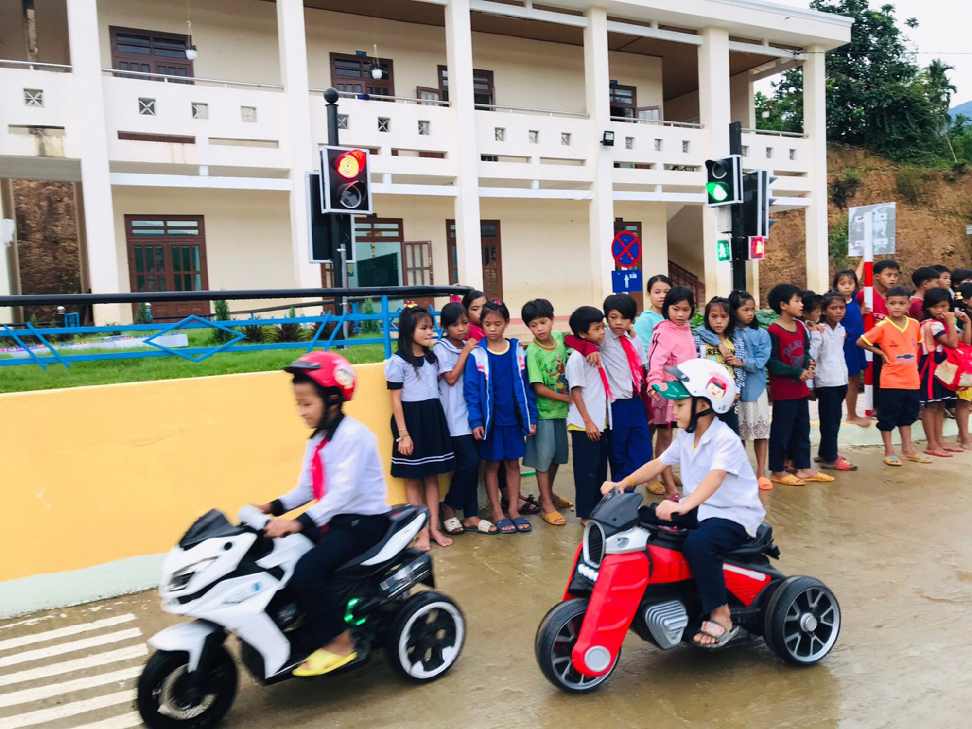 Two students drive electric toy bikes on an obstacle course in the schoolyard at Tra Tap Primary School in Quang Ngai Province, Vietnam. Photo: Le Trung / Tuoi Tre