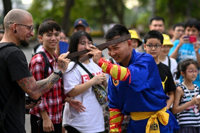A spectator touches an iron bar bent around the head of a student of the centuries-old martial art of Thien Mon Dao at the Hoan Kiem lake in Hanoi, Vietnam. Photo: AFP