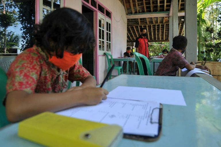 This photo taken on May 20, 2020 shows elementary school teacher Henrikus Suroto (C) conducting a class at his students' home in Magelang, Central Java, after schools were closed due to the COVID-19 outbreak. Photo: AFP