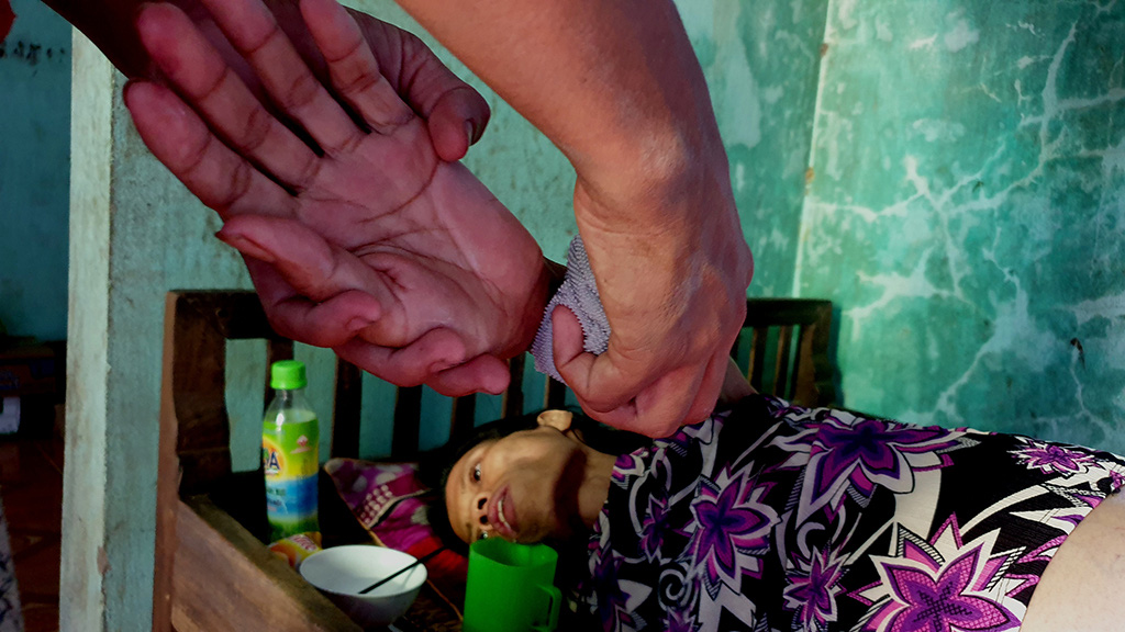 Le Viet Minh, 16, tends to his terminally-ill mother at their home in Quang Binh Province, Vietnam after quitting school to support his family financially. Photo: Q.Nam / Tuoi Tre