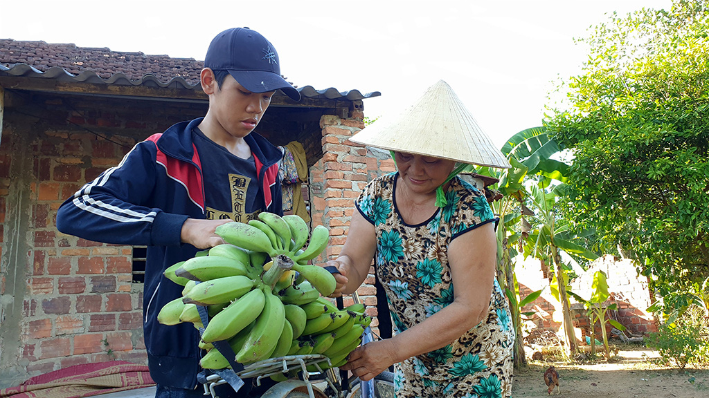 Le Viet Minh (left), 16, buys bananas from a neighbor for sale later to earn money for his family. Photo: Q.Nam / Tuoi Tre